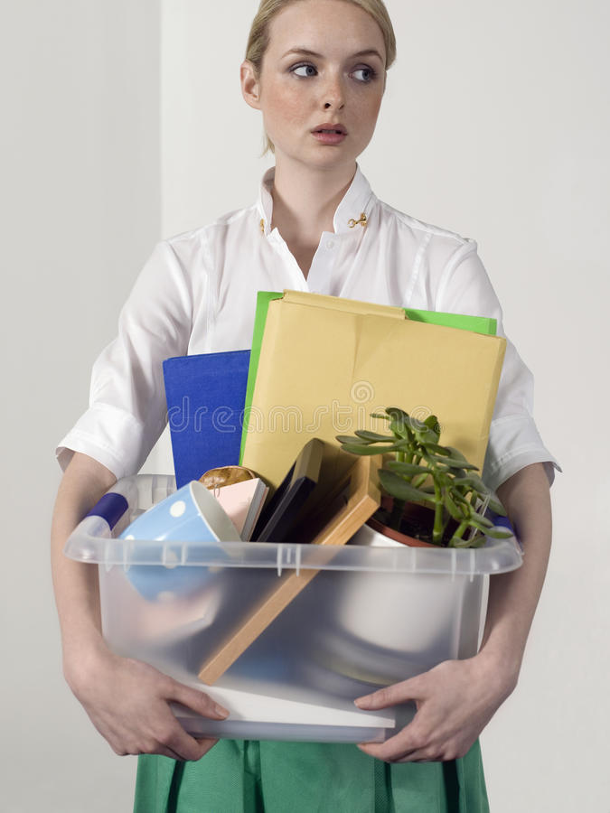 Office Worker Carrying Personal Belongings. Female office worker carrying personal belongings indoors royalty free stock images