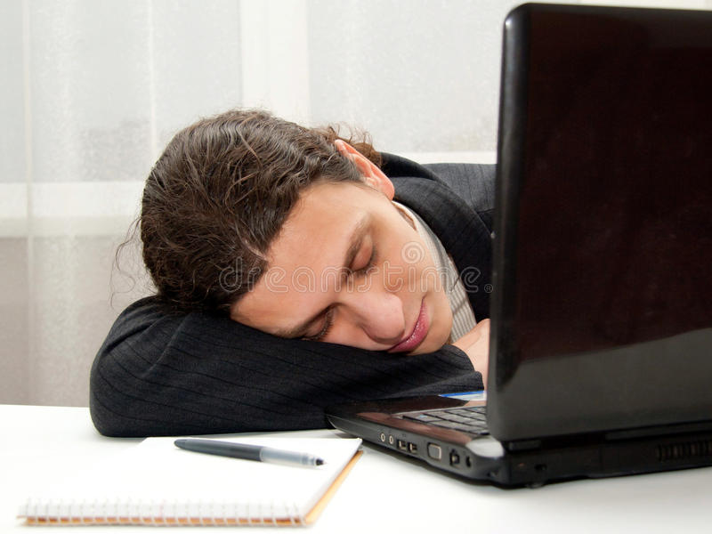 Office worker falling asleep at desk royalty free stock photography