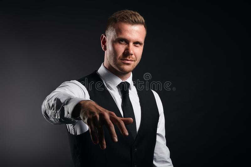 Office worker giving hand for an handshake. Funny office worker giving hand for an handshake to seal the agreement isolated on black background, busisness,man is stock photo