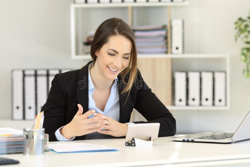 Office worker having a video call with a phone. Office worker having a video call with a smart phone on a desktop stock photography