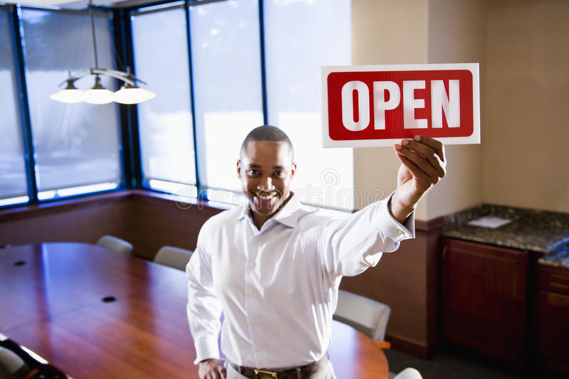 Office worker holding open sign in empty boardroom stock image