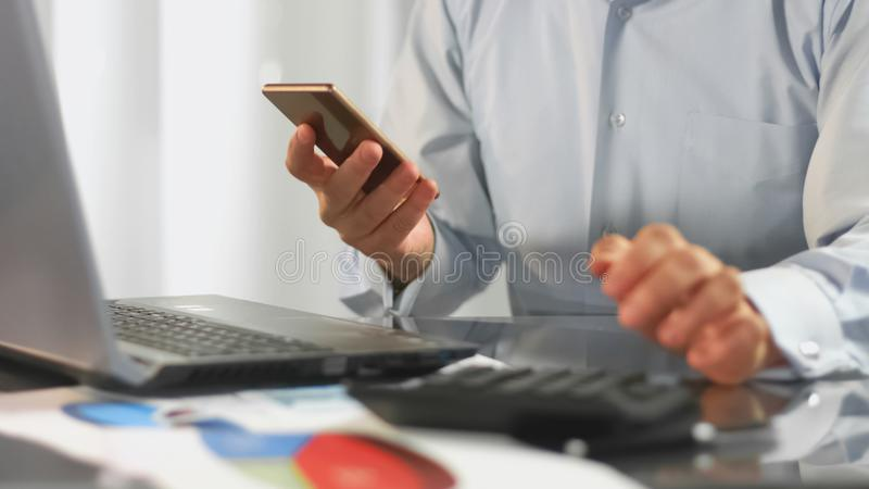 Office worker holding smartphone calling client, business communication, device. Stock photo royalty free stock photo