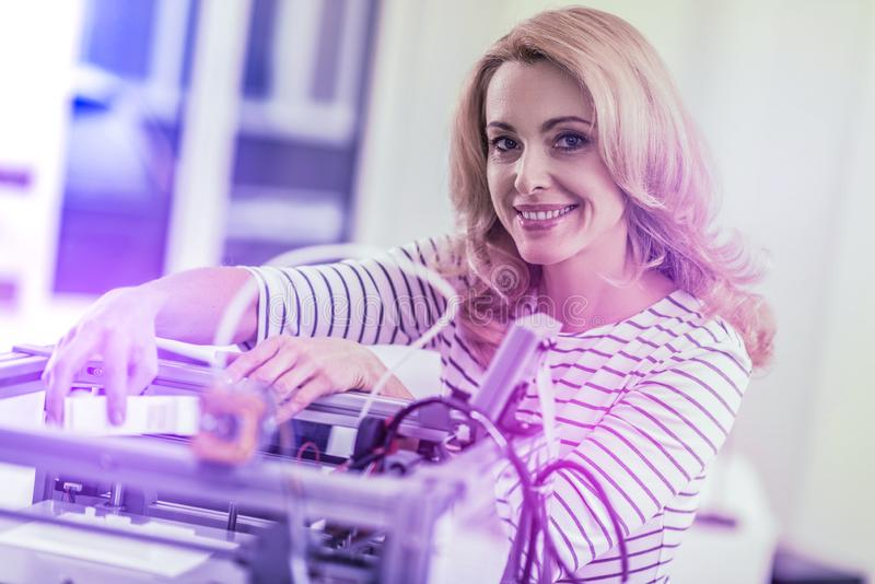 Office worker inserting new cartridge into laser printer while printing new sketches royalty free stock photo