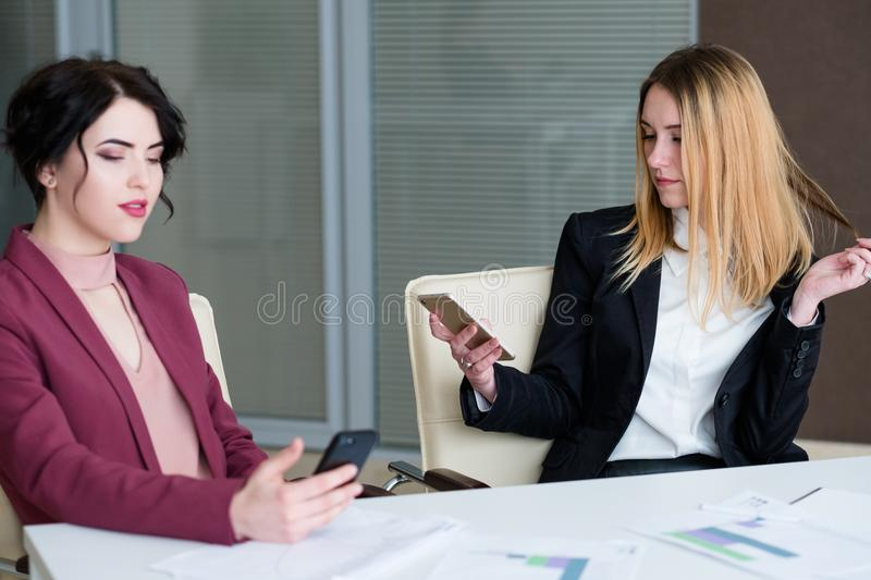 Office worker lifestyle business procrastination. Modern office worker lifestyle procrastination. lazy laid back inefficient relaxed women texting on the phone royalty free stock images