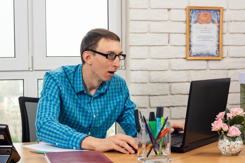 An office worker looks at the laptop screen in surprise stock photography