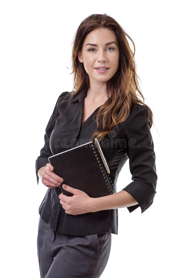 Office worker with note book. Pretty brunette holding a notebook and a pen royalty free stock image