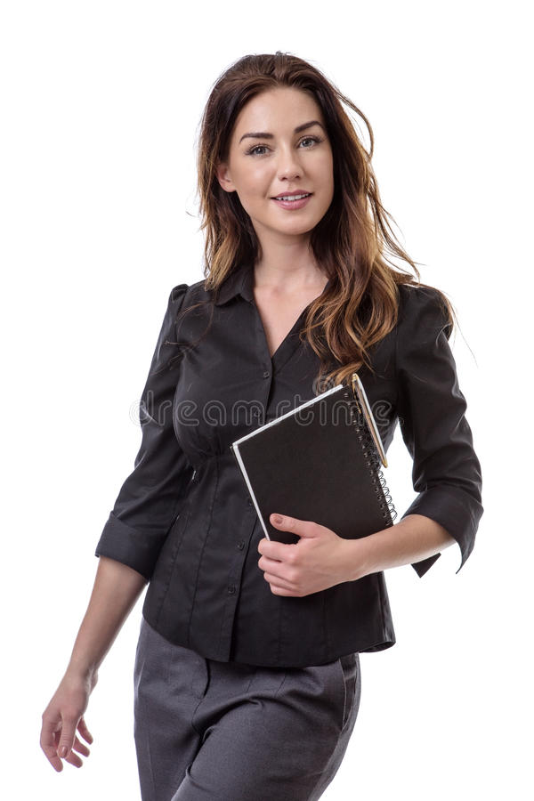 Office worker with note book. Pretty brunette holding a notebook and a pen stock photography