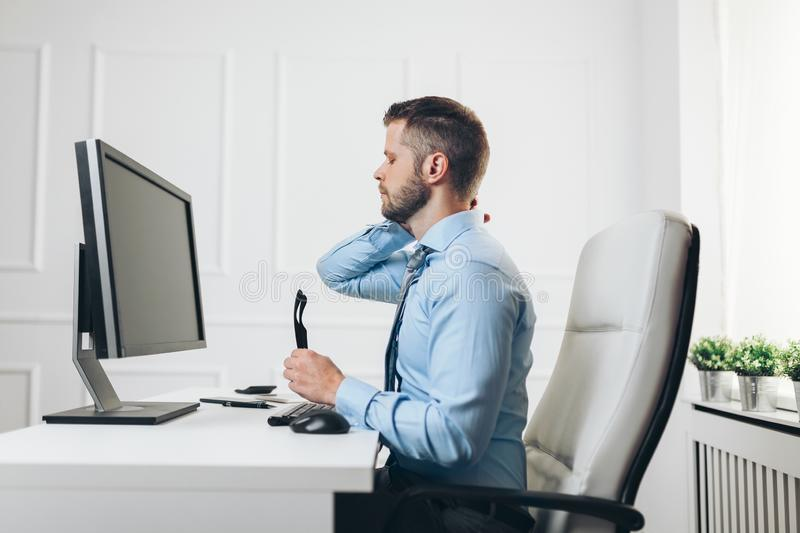 Office worker with pain from sitting at desk all day royalty free stock images