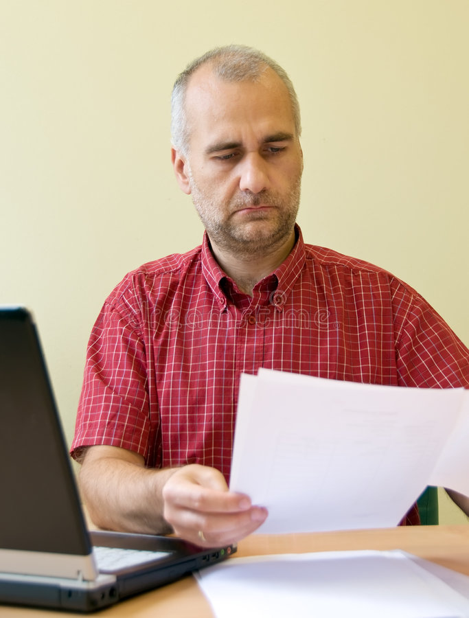 Office worker reading. Office worker doing his job at the desk with laptop royalty free stock photos
