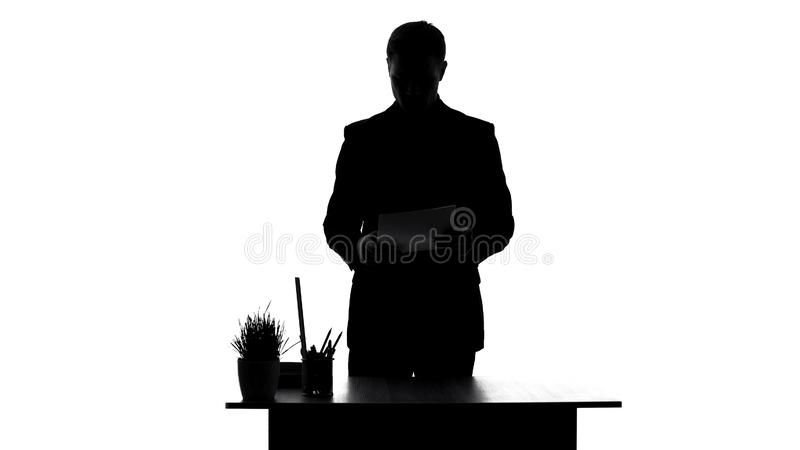 Office worker reading contract documents standing near table, analyzing report stock image
