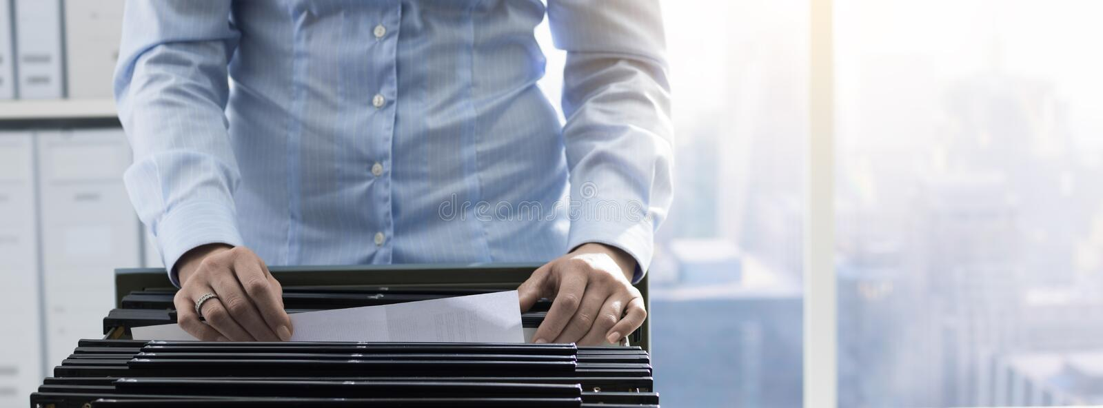 Office worker searching files in the archive. Female office worker searching files and paperwork in the archive, she is checking folders in a filing cabinet stock photo