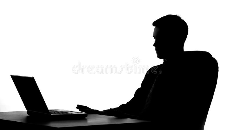 Office worker shadow sitting in front of laptop, thinking on business proposal stock photography