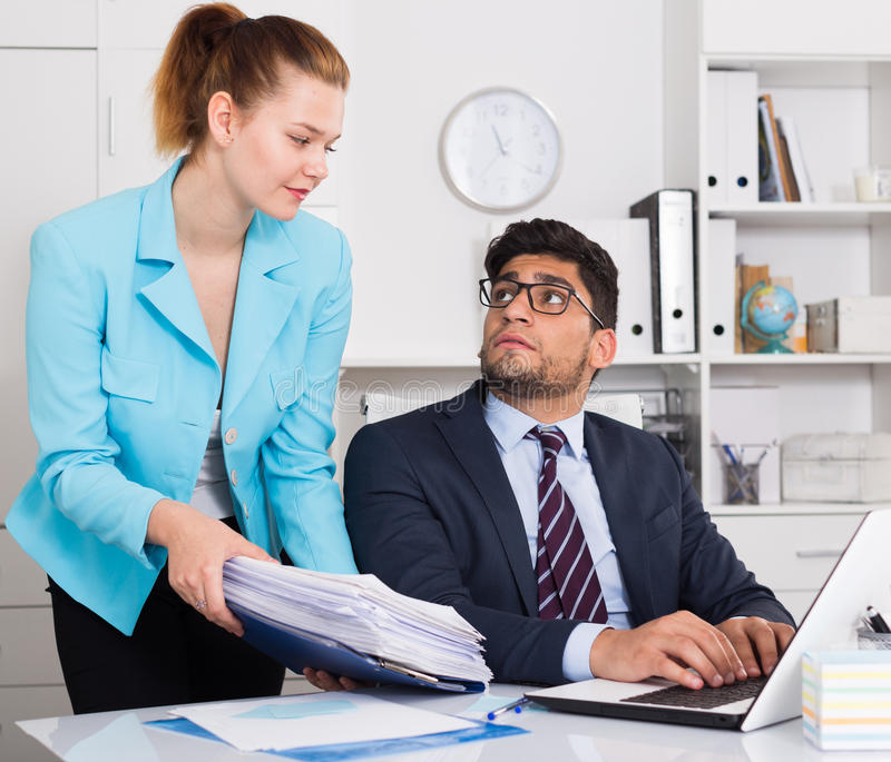 Office worker shocked by stack of papers stock photo