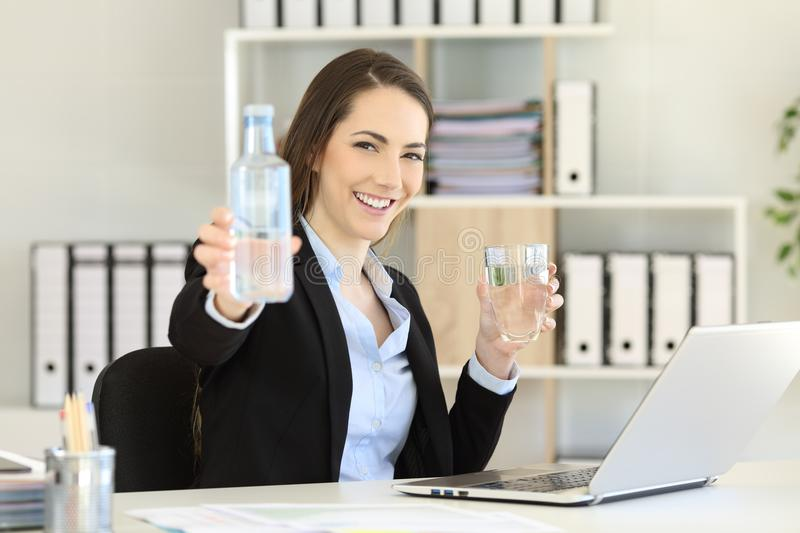 Office worker showing a bottle of water royalty free stock image