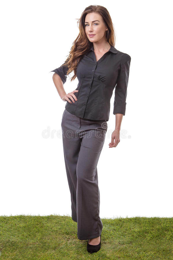 Office worker standing. Slim, pretty model who is standing on grass in a business suit, isolated on white stock photography