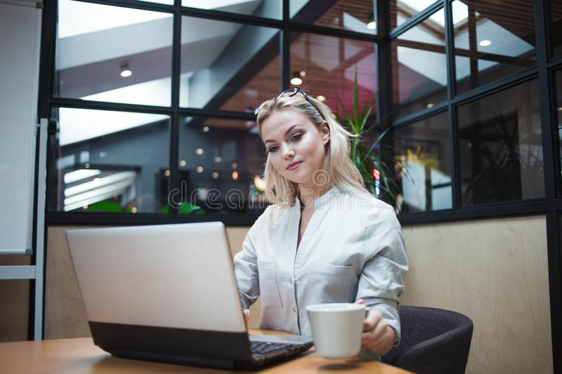 An office worker or student is working on a laptop. Happy confident blonde in a stylish office. royalty free stock photo