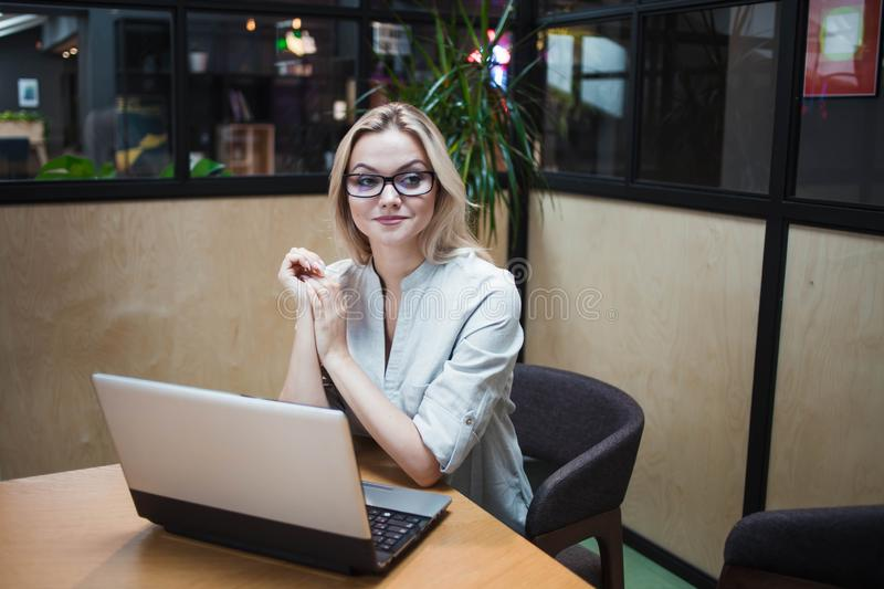 An office worker or student is working on a laptop. Happy confident blonde in a stylish office. royalty free stock photography