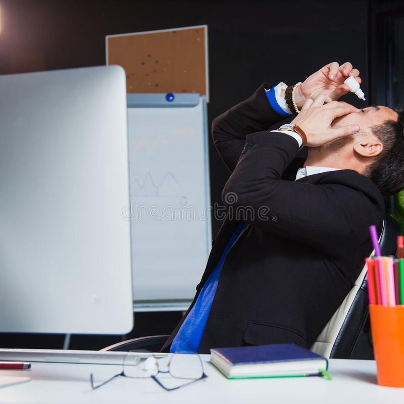 Office worker suffering dry eye syndrome, artificial tears eye drops stock images