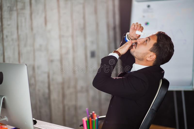 Office worker suffering dry eye syndrome, artificial tears eye drops royalty free stock photos