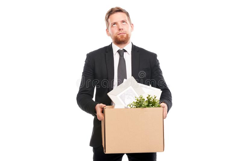 Office worker with personal belongings. Office worker in suit holding box with personal belongings on white background royalty free stock image