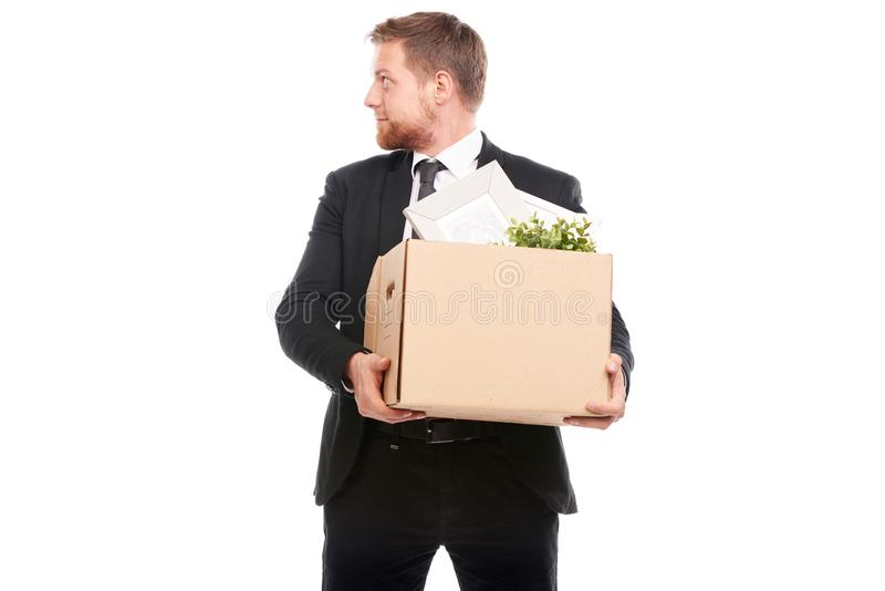 Office worker with personal belongings. Office worker in suit holding box with personal belongings on white background royalty free stock photography