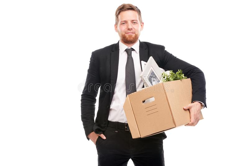 Office worker with personal belongings. Office worker in suit holding box with personal belongings on white background royalty free stock images