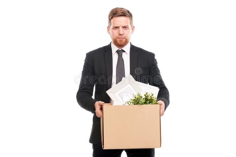 Office worker with personal belongings. Office worker in suit holding box with personal belongings on white background royalty free stock photo