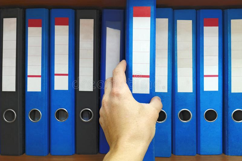 Office worker taking a folder in the archive: database, administration and file management concept. Closeup hand selecting big fol stock photography