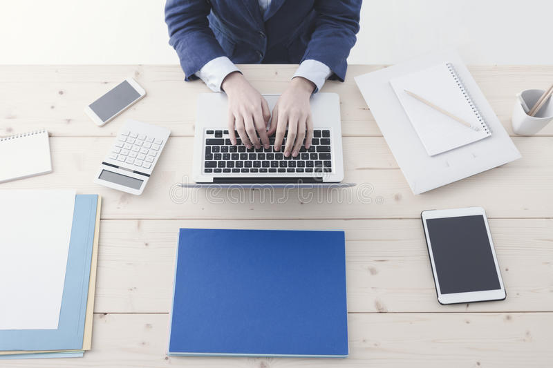 Office worker typing on a laptop stock photography