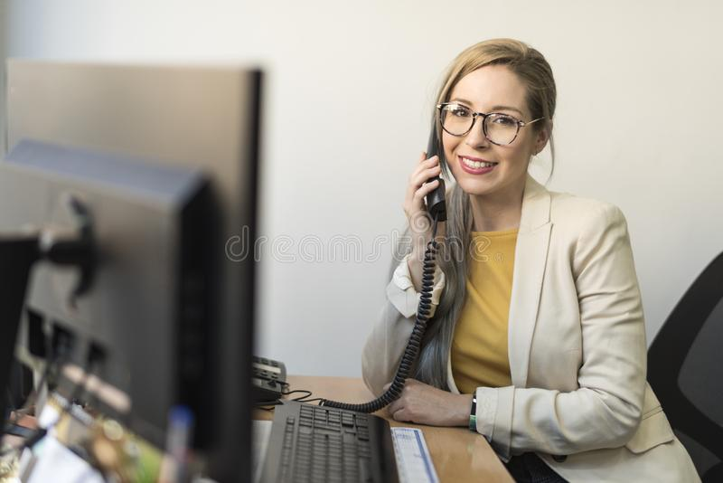 Office worker woman looking at camera in office stock images