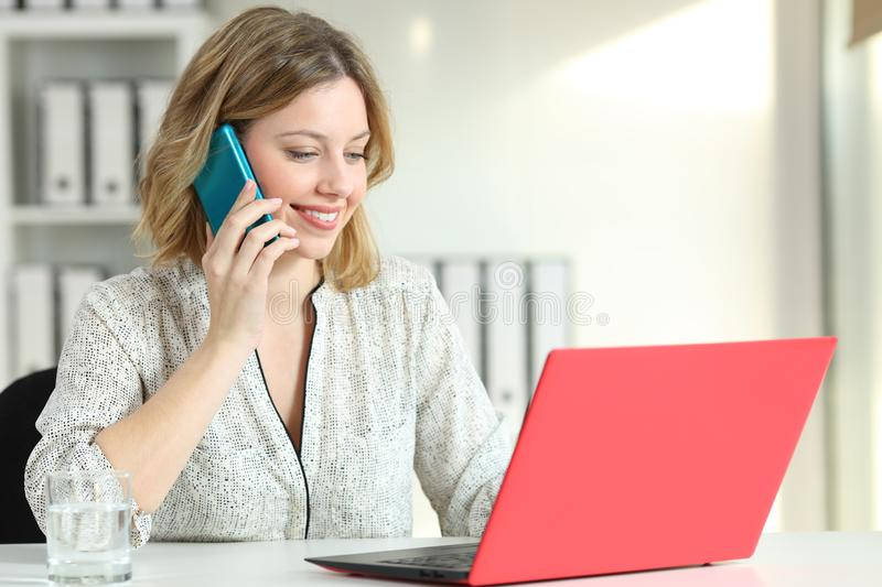 Office worker working with two colorful devices. Calling on phone and checking laptop content stock images
