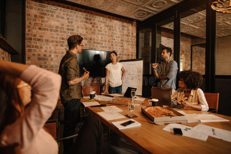 Office workers discussing new business strategy. Shot of a group of young business professionals having a meeting in boardroom. Office workers discussing new royalty free stock photo