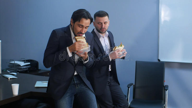 Office workers have a break from work to eat second breakfast. Professional shot in 4K resolution. 085. You can use it e.g. in your commercial video, business royalty free stock photos