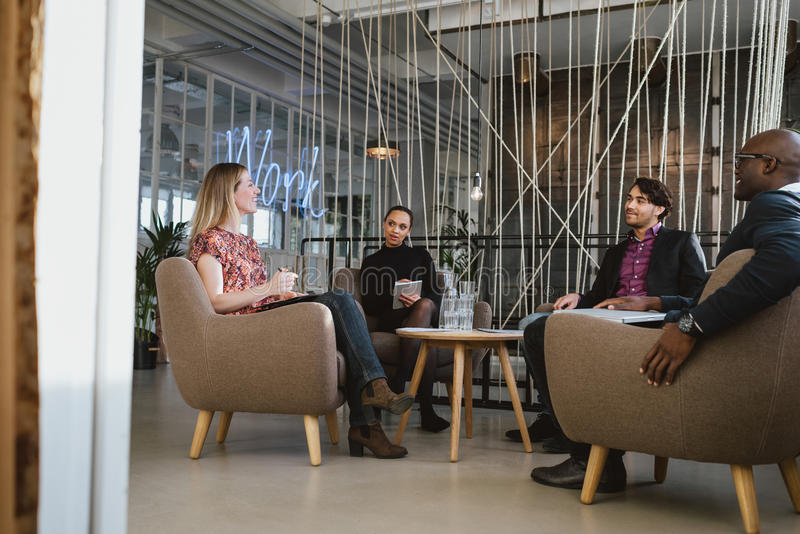 Office workers having a meeting in lobby. Happy young people sitting together in office discussing business. Office workers having a meeting in lobby. Diverse royalty free stock photo