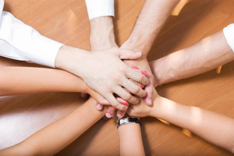 Office workers hold hands together. On table stock image