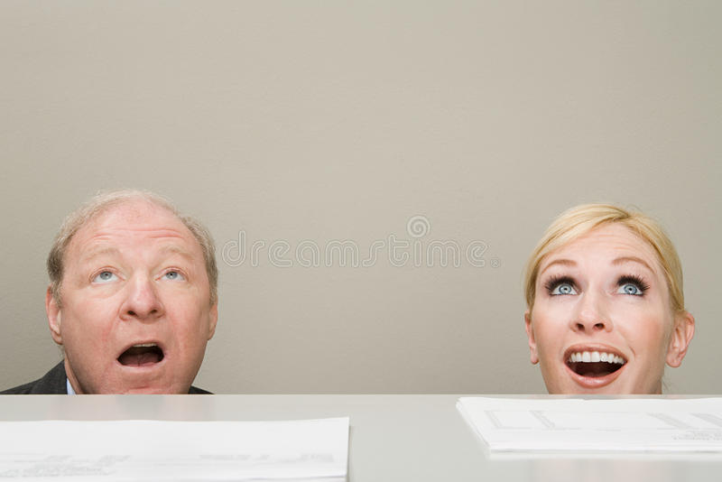 Office workers looking up in surprise stock photography