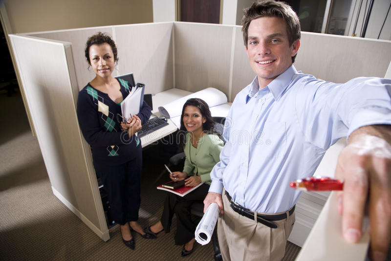 Office workers meeting in a cubicle. Multiethnic office workers meeting in a cubicle royalty free stock photos