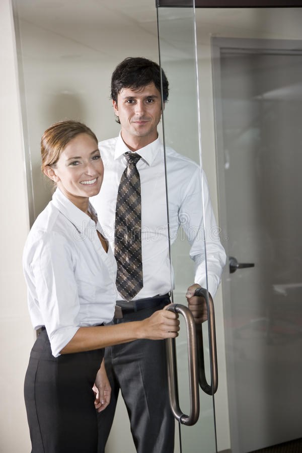 Office workers opening glass door. Two business people at door of office boardroom stock images