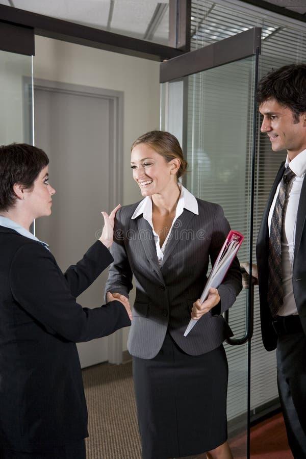 Office workers shaking hands at door of boardroom. Three office workers shaking hands at door of boardroom stock photo
