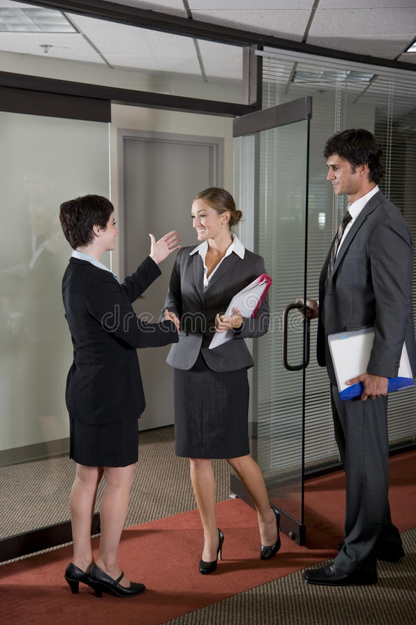 Office workers shaking hands at door of boardroom. Three office workers shaking hands at door of boardroom royalty free stock photography
