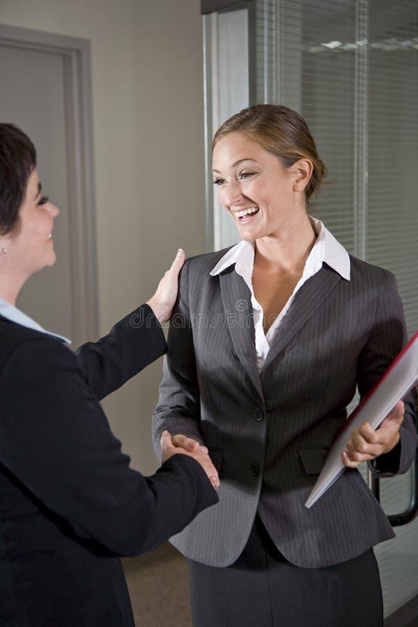Office workers shaking hands at door of boardroom. Two female office workers shaking hands at door of boardroom stock photo
