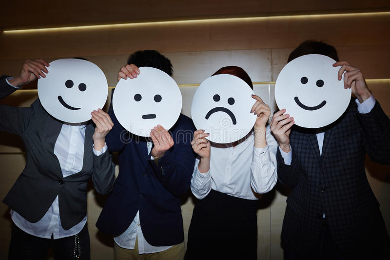 Office Workers Trying on Smiling and Sad Masks stock image