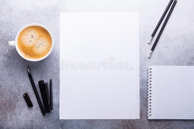 Office workplace with blank paper, cup of coffee, note pad and pen. Stone background. Top view stock photos