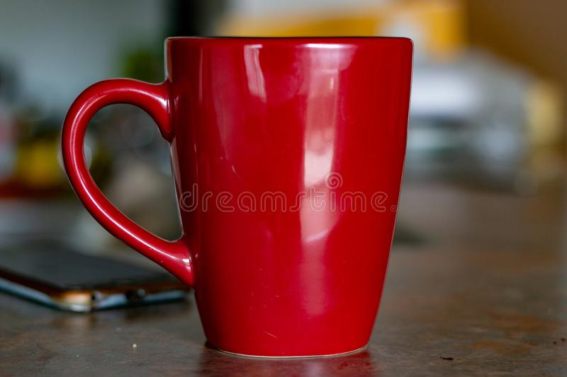 Office workplace with coffee and charts on wooden desk table in front of window with blinds. stock photo