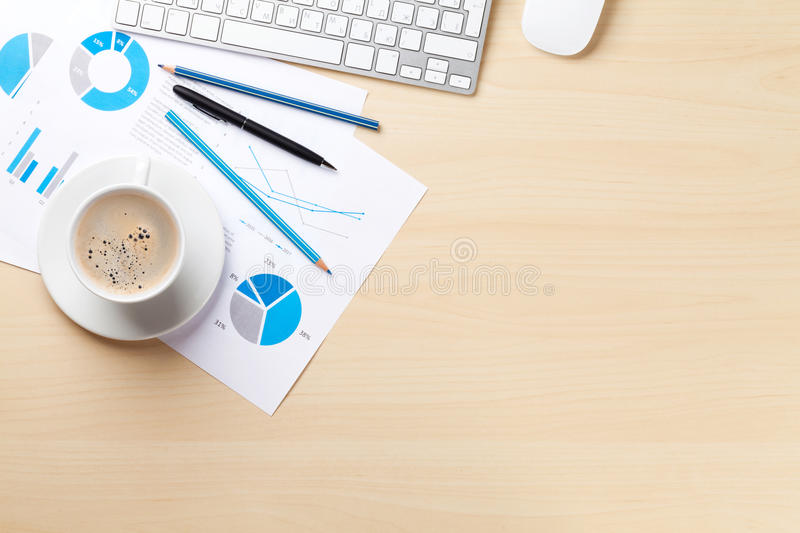 Office workplace with coffee cup and charts. Office desk workplace with pc, charts and coffee on wooden table. Top view with copy space stock photos