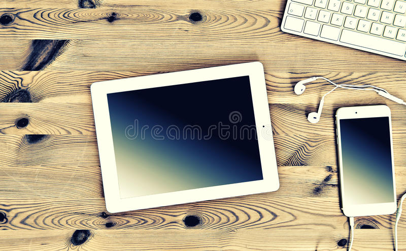 Office Workplace with Keyboard, Tablet PC, Phone. Vintage Instagram style royalty free stock images