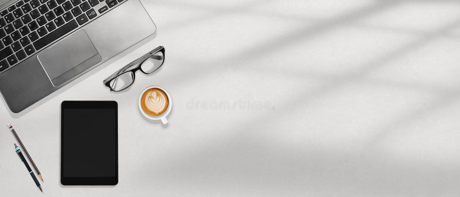 Office workspace flatlay laptop, tablet, eye glasses and coffee on the white desktop royalty free stock images