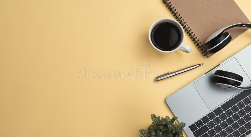 office workspace yellow desk table with laptop, coffee, mobile, notebook, plant stock images