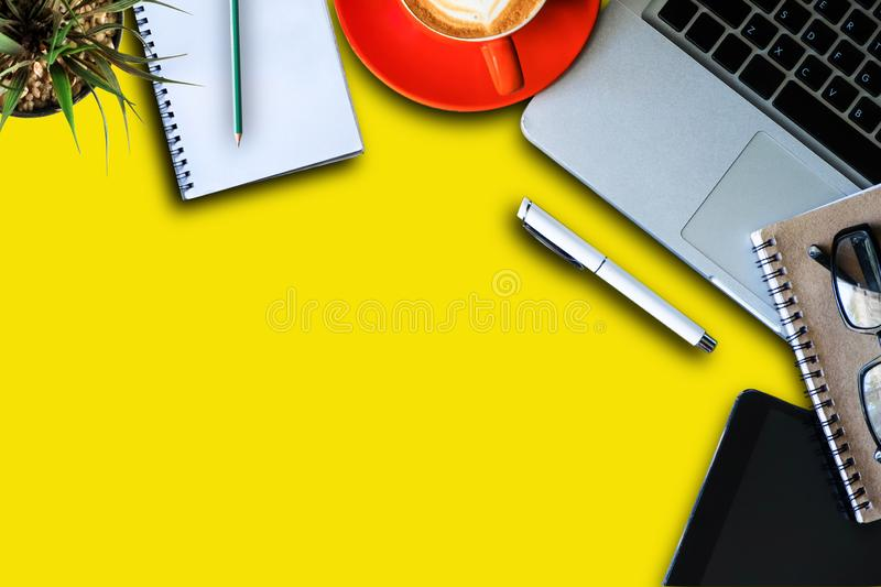 Office yellow workplace backdrop with coffee cup, supplies and computer. royalty free stock images