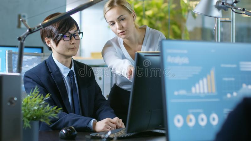 In the Office Young Businesswoman Sitting at Her Desk Talks with stock photo